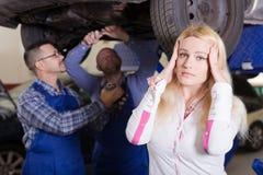 设法两位的技工在车间欺诈客户 免版税库存图片