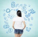 设法做出选择倾向于有些体育活动一个深色的夫人的一个背面图 得出蓝色体育象  免版税库存照片