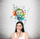 设法创造某一企业项目或专题研究的一个新的想法一个年轻狡猾的深色的夫人的画象 一五颜六色 免版税库存图片