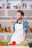 设法微笑的年轻的人烹调晚餐在厨房里 库存照片