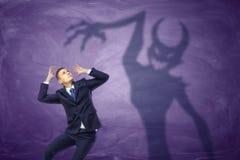 设法恶魔的阴影捉住害怕商人 免版税图库摄影
