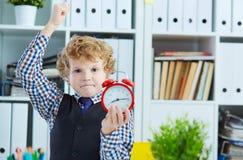 设法恼怒的男孩猛击闹钟,站立在办公室 缺乏时间,不愉快的经历管理,超时 库存图片
