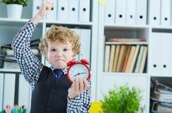 设法恼怒的男孩猛击闹钟,站立在办公室 缺乏时间,不愉快的经历管理,超时 免版税库存图片