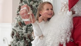 设法愉快的矮小的微笑的女孩猜测什么是在她的从圣诞老人的圣诞节礼物里面 库存图片