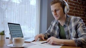 设法接近的观点的一个年轻的钢琴演奏家或的吉他弹奏者组成他在一个离开的咖啡馆duting的咖啡休息的新的歌曲 股票视频