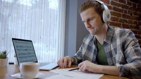 设法接近的观点的一个年轻的钢琴演奏家或的吉他弹奏者组成他在一个离开的咖啡馆duting的咖啡休息的新的歌曲 股票录像