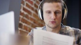 设法接近的观点的一个年轻的钢琴演奏家或的吉他弹奏者组成他在一个离开的咖啡馆duting的咖啡休息的新的歌曲 影视素材