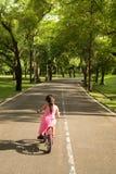 设法桃红色的礼服的小女孩骑自行车朝向为一条狭窄的街道在公园 免版税图库摄影
