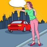 设法流行艺术的妇女捉住在城市道路的一辆汽车 库存照片