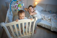 设法疲乏的年轻的母亲画象投入睡觉她失眠的男婴 库存照片