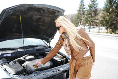 设法白肤金发的女孩修理被中断的汽车 免版税图库摄影