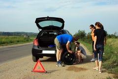 设法的人们修理一个泄了气的轮胎 库存照片