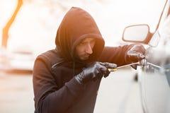 设法的偷车贼闯进有螺丝刀的一辆汽车 免版税库存照片