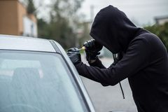设法的偷车贼闯进有螺丝刀的一辆汽车 免版税图库摄影