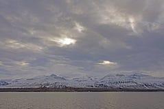 设法的太阳打破在沿海山 库存图片