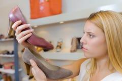 设法的夫人决定在两双鞋子之间她举行 免版税库存照片