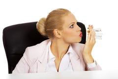设法的女商人坐在书桌后和抽一些根香烟 库存照片