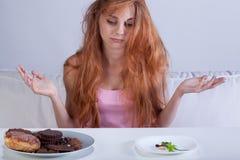 设法的女孩克服甜点的饥饿 免版税库存图片