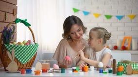 设法的女孩绘复活节彩蛋,帮助和支持她的爱的母亲 股票视频