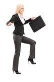 设法的女实业家拿着公文包和保持平衡 免版税库存图片