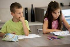 设法的小男孩复制他的朋友家庭作业 免版税库存照片