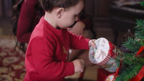 设法的小男孩打开他们的有礼物的箱子他自己 照顾观看她的儿子,在圣诞节附近坐 影视素材