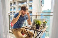 设法的年轻人在大厦工作懊恼的阳台工作外面 噪声概念 空气污染从 免版税库存照片