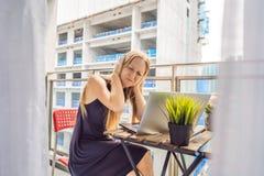 设法的年轻女人在大厦工作懊恼的阳台工作外面 噪声概念 空气污染从 免版税库存照片