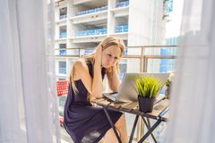 设法的年轻女人在大厦工作懊恼的阳台工作外面 噪声概念 空气污染从 免版税库存图片