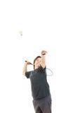 设法的男孩微笑和拿着羽毛球拍和击中球 免版税库存图片
