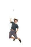 设法的男孩拿着羽毛球拍和击中球 免版税库存图片