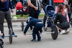 设法的节日的男孩提高举重标准 免版税库存图片