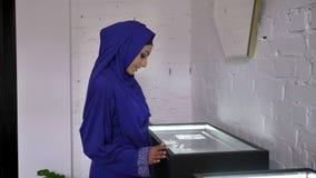 设法的hijab的年轻回教妇女看与辅助部件的显示在首饰店和决定怎样买 股票录像