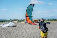 设法的Kitesurfer举他的力量风筝在天空中在海滩 免版税库存照片