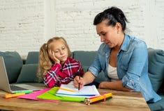 设法绝望的妇女帮助她的学习和做家庭作业的女儿,当女孩是抱怨乏味学习时 免版税库存照片