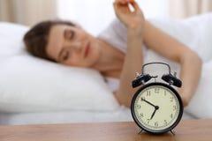 设法美丽的睡觉的妇女休息在床上和醒与闹钟 图库摄影