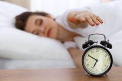 设法美丽的睡觉的妇女休息在床上和醒与闹钟 免版税库存照片