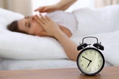 设法美丽的睡觉的妇女休息在床上和醒与闹钟 库存图片