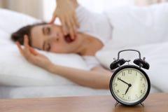 设法美丽的睡觉的妇女休息在床上和醒与闹钟 免版税库存图片