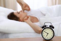 设法美丽的睡觉的妇女休息在床上和醒与闹钟 免版税图库摄影