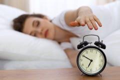 设法美丽的睡觉的妇女休息在床上和醒与闹钟 库存照片