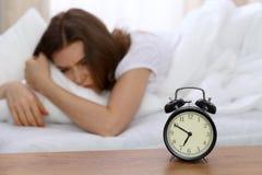 设法美丽的睡觉的妇女在床上和醒与闹钟 有的女孩与早早起来的困难 免版税库存照片