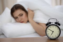 设法美丽的睡觉的妇女在床上和醒与闹钟 有的女孩与早早起来的困难 免版税库存图片