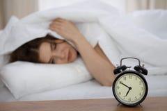 设法美丽的睡觉的妇女在床上和醒与闹钟 有的女孩与早早起来的困难 库存图片