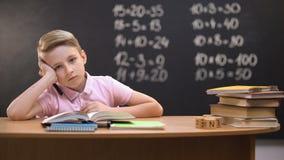 设法被超载的男小学生坐在书桌和解决任务困难的等式 股票录像