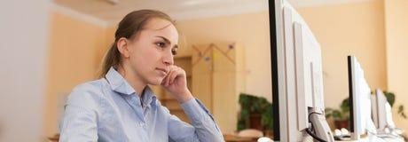 设法被集中的女实业家在办公室解决在线的一项困难的任务在一台台式计算机 库存照片