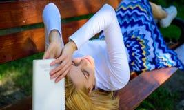 设法记住 乏味文学 妇女疲倦了面孔放松在庭院阅读书的作为断裂 女孩位置长凳放松 库存照片