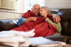 设法资深的夫妇在家保留温暖的下面毯子 免版税库存照片