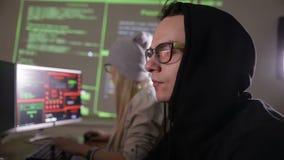 设法年轻人和妇女的黑客对计算机系统能够存取 股票录像