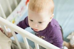 设法婴孩的顶视图站起来在他的轻便小床 免版税库存照片
